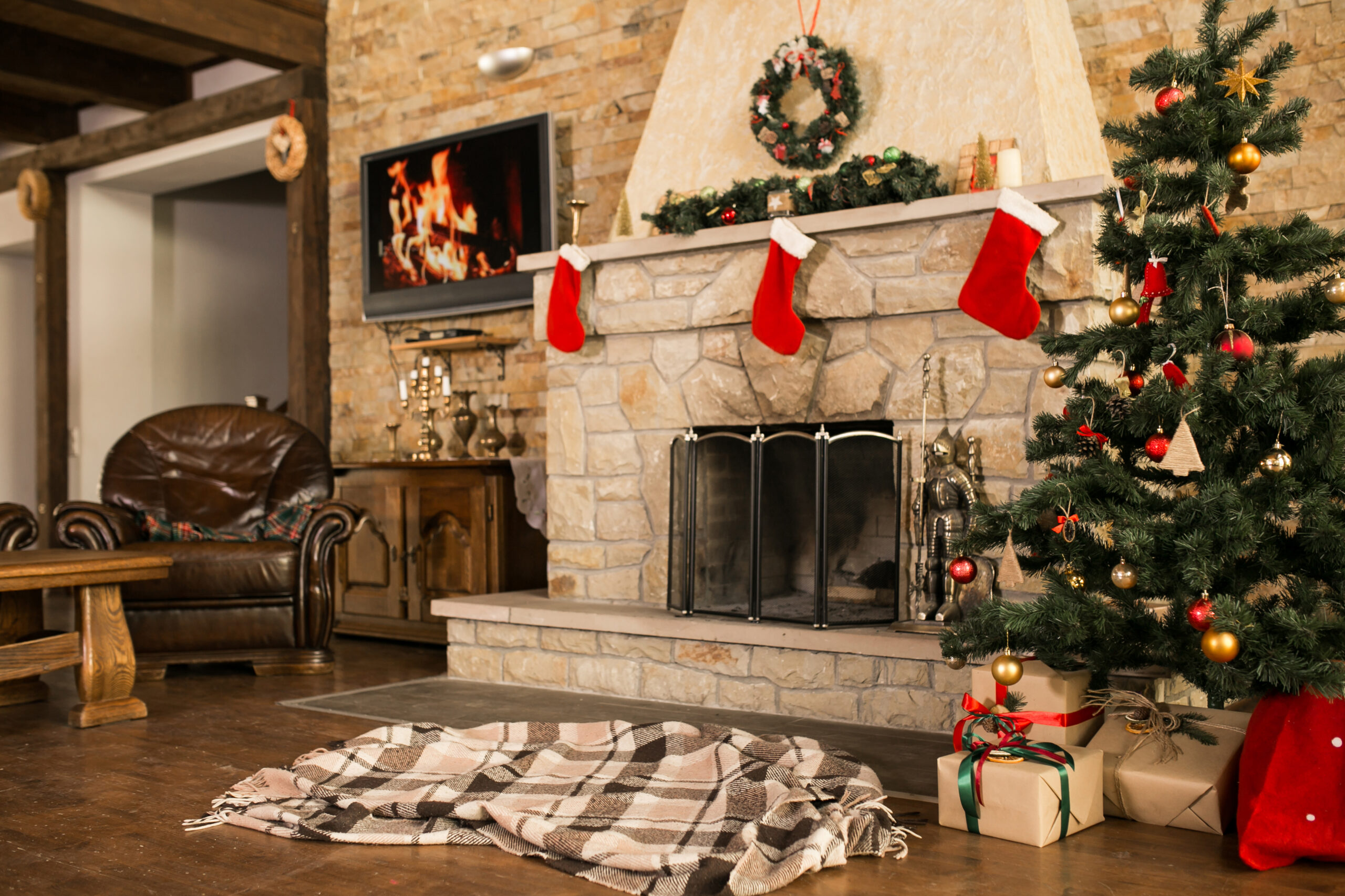 Indoor holiday decor with Christmas tree and fireplace.