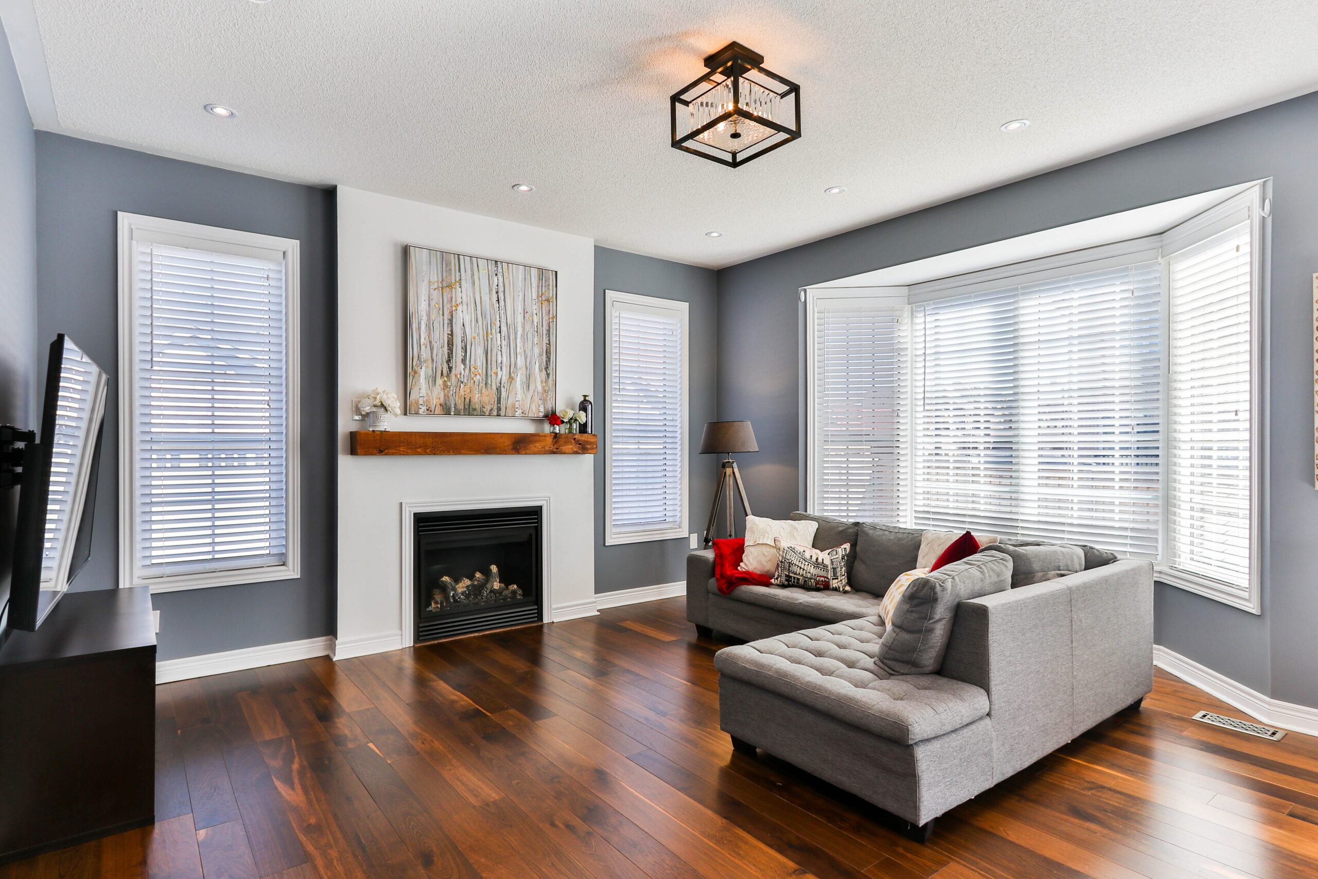 Living room with gray walls and white brick fireplace. Furnished with gray couch.